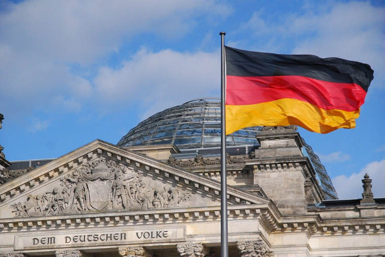 german red black and yellow flag in front of reichstag parliamentary building in berlin