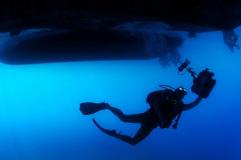 a scuba diver with underwater camera equipment in hand ascending to two boats waiting on the surface
