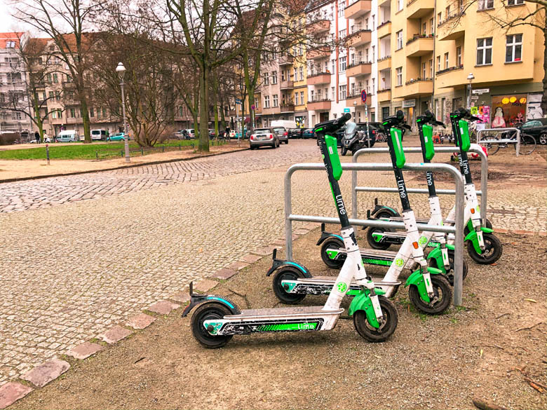 a row of lime electric scooters in berlin