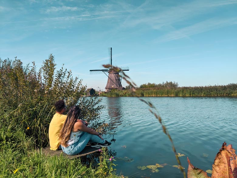 best photography spot in the netherlands with a couple sitting next to the river and a traditional windmill in the background